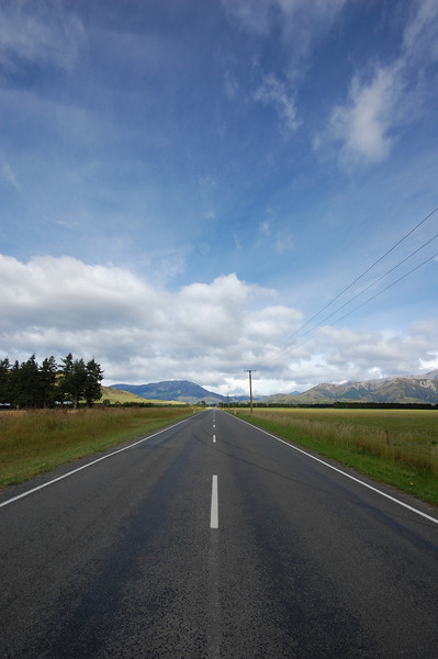 New Zealand has miles and miles of empty two lane roads that pass through beautiful, uninhabited landscapes. During one of our long drives through the countryside, I walked to the middle of this straight road that goes on as far as the eye can see to capture our roadtrip.
