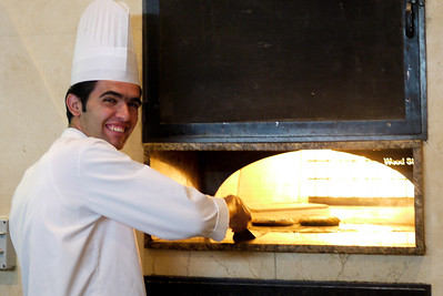 Chef making baked pita bread with za'atar for breakfast.