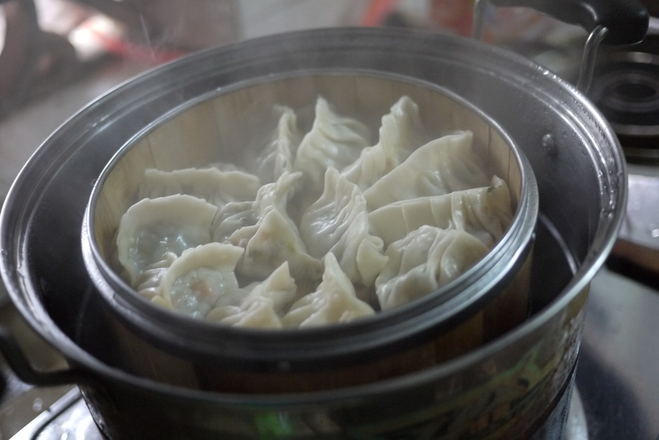 Steaming Chinese dumplings in a pot at a cooking class in the kitchen class at our hostel in Yangshuo, China