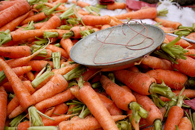A scale and carrots rest as bustling activity passes by at the weekly Fuli Market near Yangshuo, China