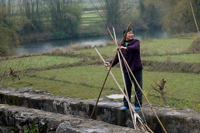 This woman is moving the dammed water with the help of friends nearby outside of Yangshuo, China.
