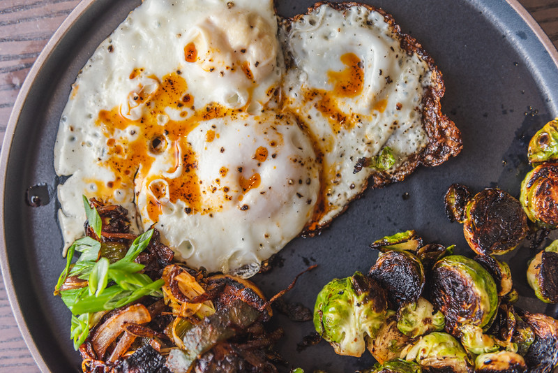 fried eggs with guajillo chili oil, sweet potato home fries, caramelized brussels sprouts