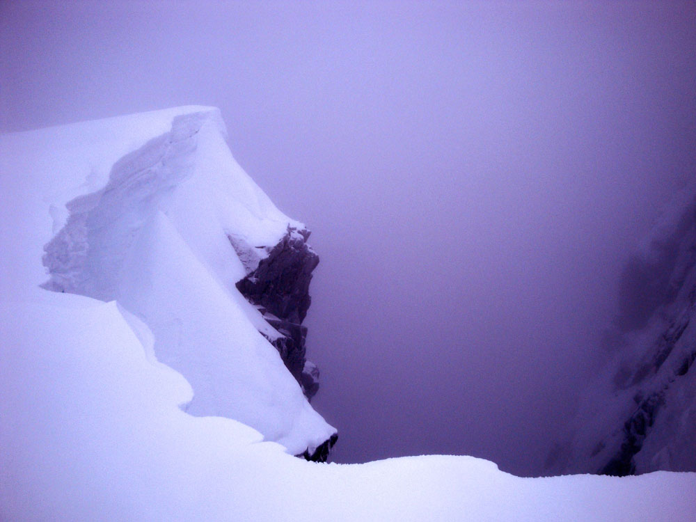 The sudden drop looming out of the murk informed us that, finally, the summit was close. We'd just stumbled onto the edge of Five Fingers Gully, into which others have fatally fallen.