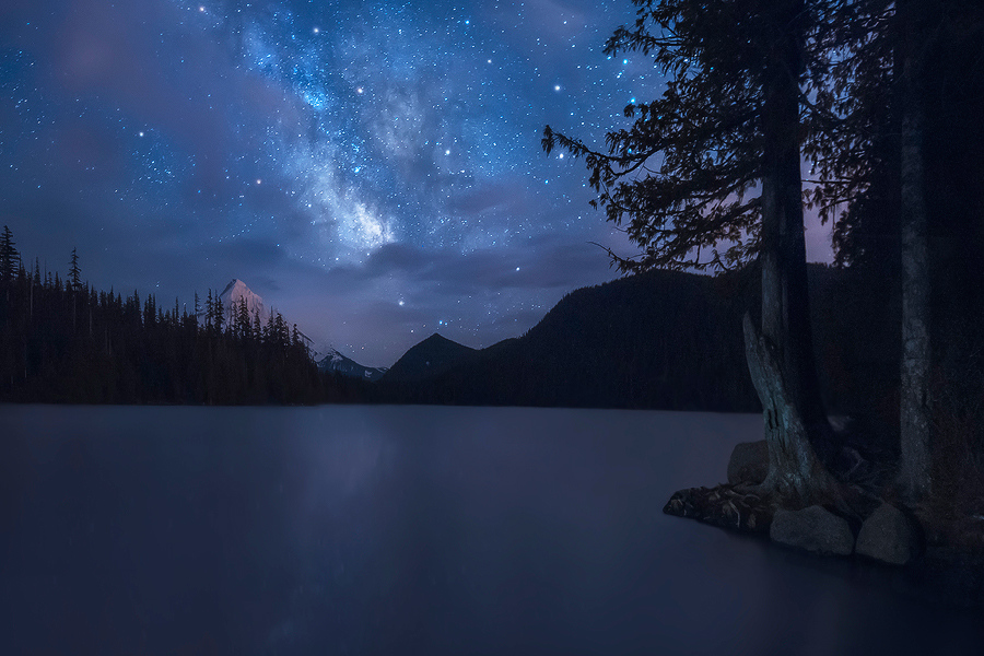 from www.DaveMorrowPhotography.comRead the full blog post -->http://www.davemorrowphotography.com/2014/05/painted-in-sky-lost-lake-oregon.htmlI've been wanting to get up to Lost Lake to shoot the Milky Way for a while now. After a few failed attempts in the past with clouds covering the sky I finally got a few shots I liked this past weekend.There were intermittent clouds, so I waited and waited and waited until the Mount Hood ( approx 11,000 feet ) and the Milky Way were visible to click off my shutter.In this photo I really wanted to convey the soft light and color tones that the stars leave on the water and surrounding landscapes when there is not much ambient city light to ruin the scene. After standing there long enough, and letting your eyes adjust, the stars twinkle brightly in the water.Thoughts, critique and comments always welcome!This is a single exposure processed in Lightroom & Photoshop.