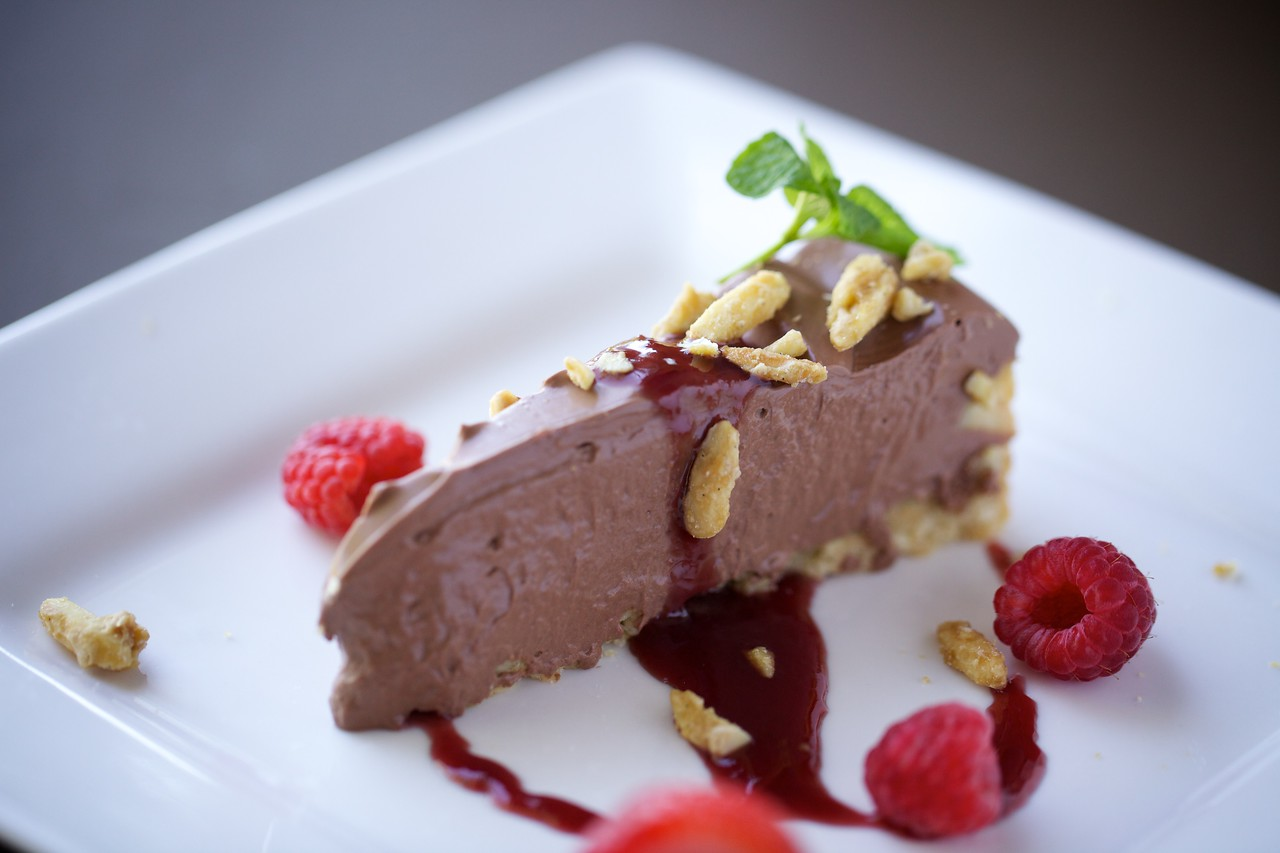 Chocolate pie with maple-glazed sliced almonds and raspberry sauce. 100% Vegan.