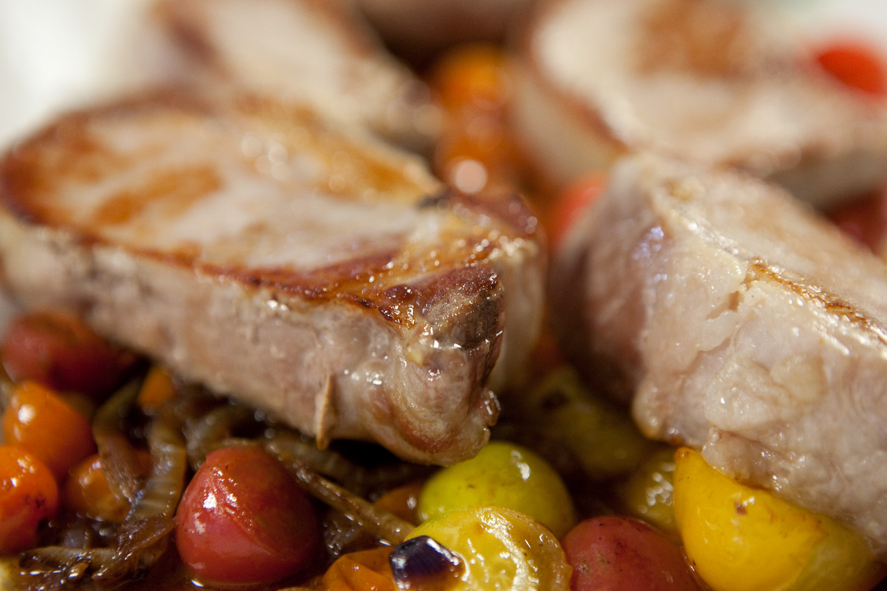 Pork chop with caramelized onion and softened cherry tomatoes