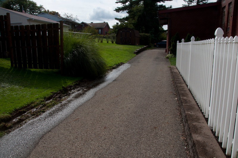 You can see the water from the neighbor's yard spilling onto to the driveway. This occurs regularly and is due in part to the spring.