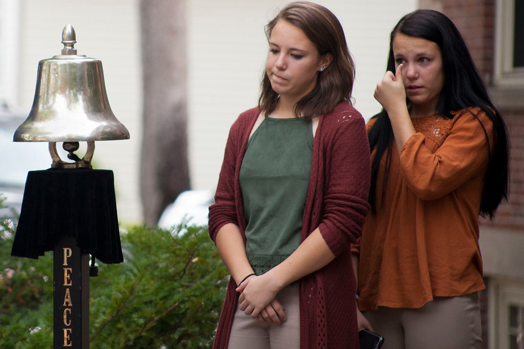 ". Lauren Thorburn (right) and Jen Thorburn, both 16, react during a ceremony marking Wednesday as ""Betsy Sawyer Day\"" flanked by a bell cast in the late teacher\'s honor. Nashoba Valley Voice/Chris Lisinski"
