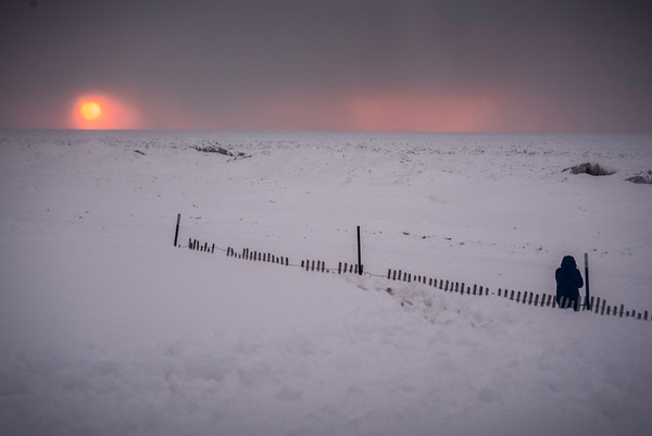 Fence on icy lake at sunset