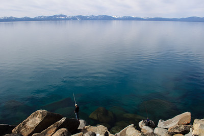 Fisherman on shoreline near Logan Shoals Vista, Lake Tahoe, Nevada, February 2012.
