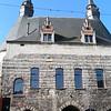 Oorspronkelijk was er ook een voorpoort met 2 ronde torentjes, maar die is verdwenen. Rond 1400 werd het gebouw, dat in Doornikse steen is opgetrokken, verhoogd met lichter gekleurde Balegemse steen. Naast de Doornikse steen, doen ook de spitsbogen denken aan de Scheldegotiek. Het dak dateert uit de 17e eeuw. De stadsomwallingen van Mechelen verdwenen pas in het begin van de 19de eeuw.