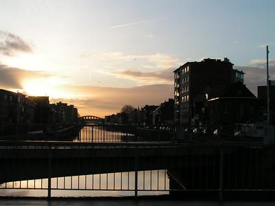 """""""De Leuvense Vaart"""" Ons beginpunt van de 'Historische Wandeltocht'. Zicht op 'De Vaart' richtig station. Op de achtergrond de spoorwegbrug. 1933-35: constructie van de meest zuidelijke Vierendeelbrug over de Leuvense vaart. Op 5 mei 1935 werd de brug """"ingereden"""" door de eerste trein met electrische tractie in België."""