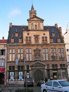 """Op 'De graanmarkt of De Korenmarkt' Het """"Hof van Sint-Joris"""" Terwijl in de 13de eeuw het Lakenhuis op deze plaats gevestigd was, werd het pand in de 15de eeuw het 'Hof van Schoofs' genoemd, naar de toenmalige eigenaars. In 1474 werd het pand verkocht aan Jean Carondelet, de eerste voorzitter van de Grote Raad, en daarna aan een Duits koopman zodat het huis 'Den Duitsch' geroemd werd."""
