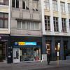 """""""Atlantis"""" Reisbureau van mijn oom Léo & tante Liliane. Met ook een geklasseerde gevel!<br /> Ernaast, huis: 'DE RAM' Guldenstraat 20<br /> 'De Ram', een classicistische gevel uit het laatste kwart van de 18de eeuw, toont op de foto nog de oorspronkelijke benedenverdieping. Na de Tweede Wereldoorlog wordt ze verbouwd tot opengewerkte winkelarcade. De rechthoekige vensters hebben typische Lodewijk XVI-omlijstingen met slingers en rosetten. De naam 'Ram' is veel ouder dan de gevel, want al in 1294 behoort het pand onder die naam toe aan de commanderij van Pitzemburg."""
