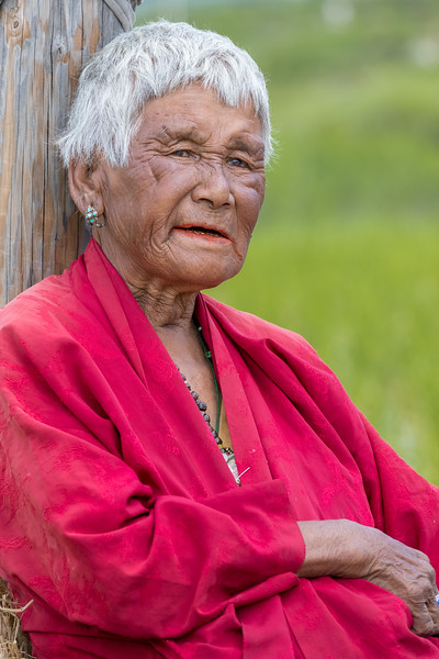 Sopsokha, Bhutan. A woman farmer (who was also chewing doma or beetlenut) listens to the reading of the Divine Madman's biography. He is credited with encouraging the use of phallic symbols, including phallus paintings on the wall of village homes. This advice is widely followed in the villages of Bhutan.