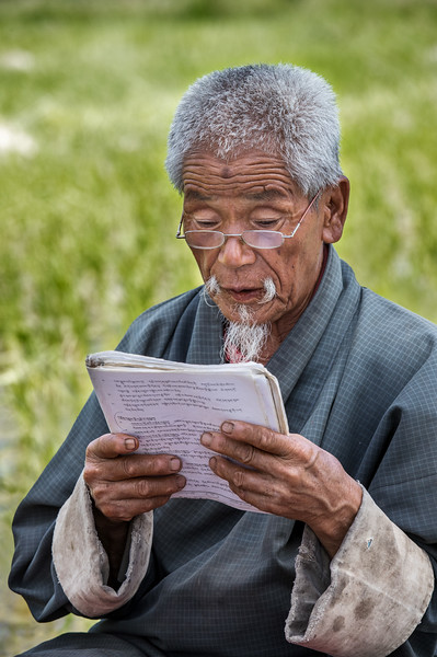 Sopsokha, Bhutan. A farmer reads aloud from a biography of the Divine Madman, so named for his unorthodox ways of teaching Buddhism, including some that were bizzare and shocking,  with sexual overtones.