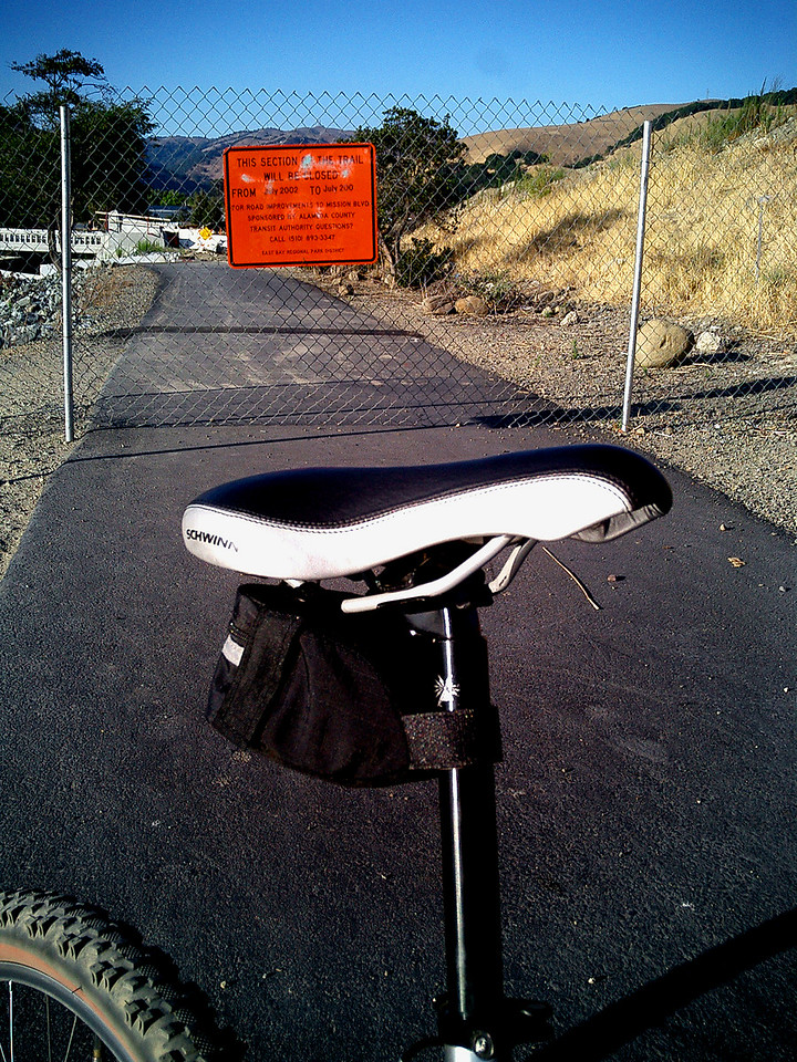 """August 3, 2004 - 10.6 Miles. Andrew adjusted his seat but forgot to tighten it down. 10.6 miles of a sliding and tilting seat was not fun. Next on the to buy list - tools! <br /> Met a fellow cyclist on the trail - Garrett - He stopped us to ask if we had a cell-phone. Garrett spotted what he believed to be stolen and abandoned goods on the side of the bike trail. We called the police and while we waited for them to arrive we talked about how lucky we are to have such a great bike trail in our own backyard. Luckily for Andrew, Garrett had a full set of tools so Andrew was able to tighten his wayward seat. Police showed up put on their blue gloves sorted through the """"stolen"""" goods and thanked us for being good citizens. We said bye to Garrett and headed home. Andrew asked if I had taken pictures of the cops and the goods for my web log - doh!"""