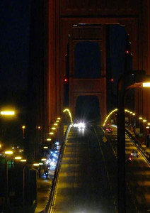 Bicycle lights are always just a little different color than a car headlight. Here the riders work their way acros the bridge as they begin the day.