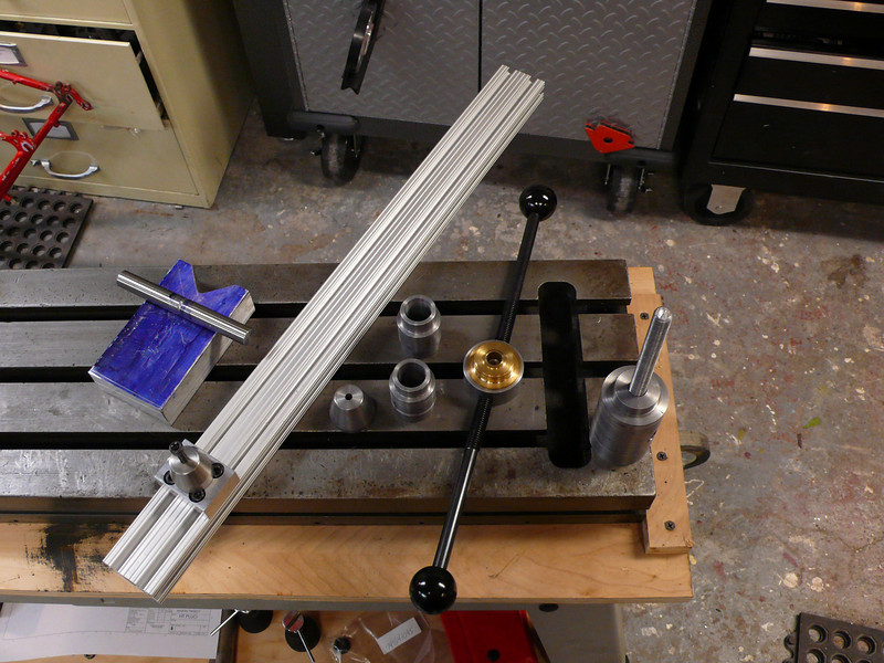 """Close up of some of the items.  From left to right:<br /> * Start of an alignment block.  The dummy axle is 135mm.<br /> * A piece of 80/20 (1020 extrusion) with a seatpost centering cone mounted on it.  You'll see how this fits together once I get the rest of my 80/20 bits.<br /> * Another cone, this will end up being used for the headtube.<br /> * Dummy headsets.  A 7/8"""" steel bar fits inside to be used for alignment purposes.<br /> * Bottom bracket post for frame alignment.  The same two handles can be used in the post or nut."""
