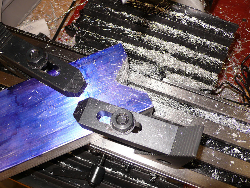 """Milling the alignment block.  I used a 45/45/90 triangle and a square to get the block at exactly 45 degrees from the milling table.  It is supported on parallel bars and clamped into place (my vise won't open wide enough for this large of a block).  I used a hack saw to rough cut the V (about 1/4"""" away from the reference lines) and then milled it clean.  It took a fair amount of time because the block is 1.5"""" thick and my end mills only have 1"""" of cutting height."""