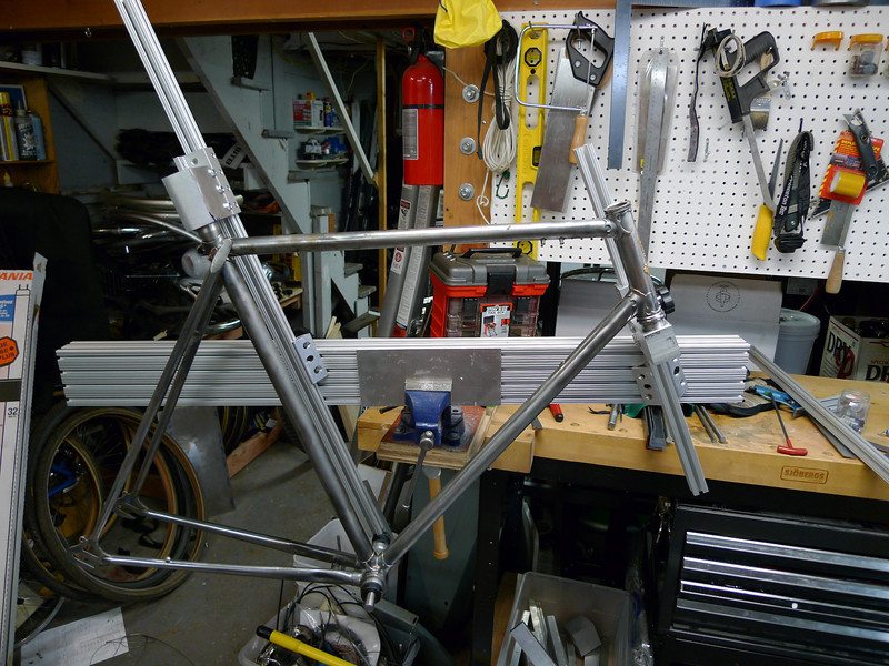 "Current jig progress.  Front triangle is mostly done.<br /> <br /> The main components are:<br /> * A center spine made out of 2040 extrusion (2"" by 4"")<br /> * Two diagonal supports, one for the HT and one for the seat tube.  Those are 1010 extrusion (1"" x 1"")<br /> * Connecting blocks to connect the diagonal supports to the main spine<br /> * Tube holders on the diagonal supports."