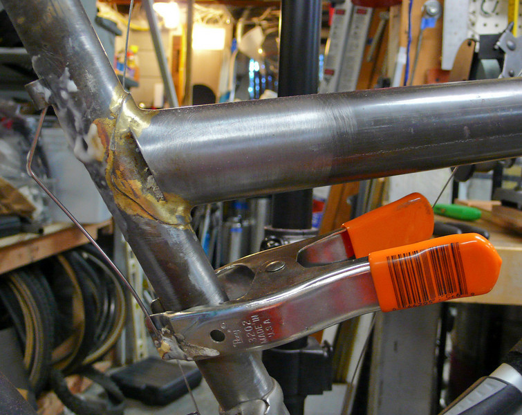 I switched the cable routing to run along the top tube so that none of the cables interfered with the rack.  Here I'm brazing on the cable housing stop for the front derailleur.  I copied this brazeon clamp fixture from Alistair Spence.
