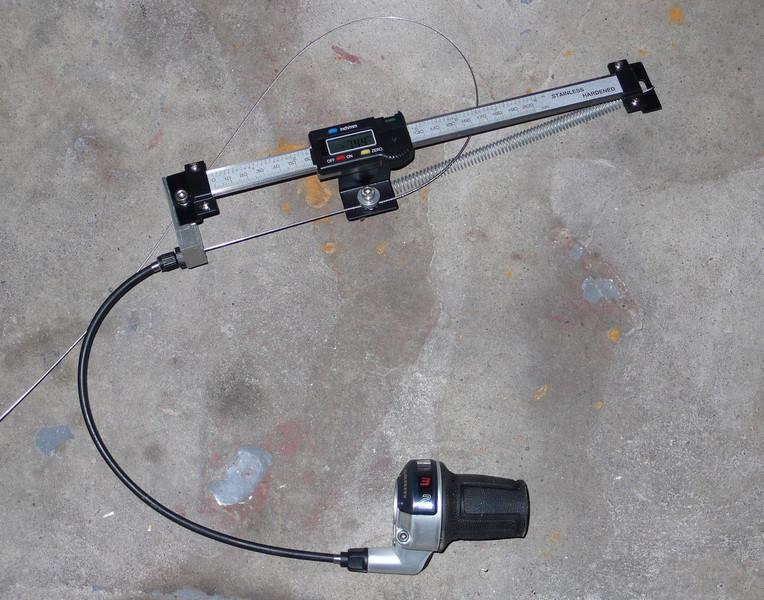 This is my shifter cable pull measuring tool.  It is simply a cheap digital scale (commonly used for digital readouts on lathes and mills) with a cable housing stop placed on one side, a clamp for the cable in the middle, and a spring on the other.  The most important thing is to have the cable housing stop in line with the cable clamp.