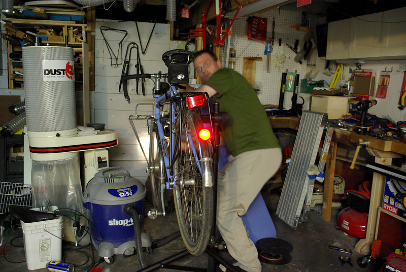 My first attempt at showing the bicycle lighting.  Half of the basement lights were on, giving ambient light similar to a late afternoon.  It's bright, but I look goofy spinning the wheel.