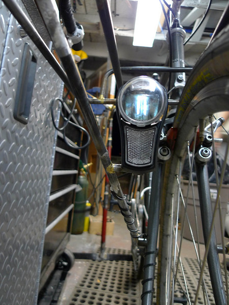 The headlight is safely tucked away between the rack stay and tire.