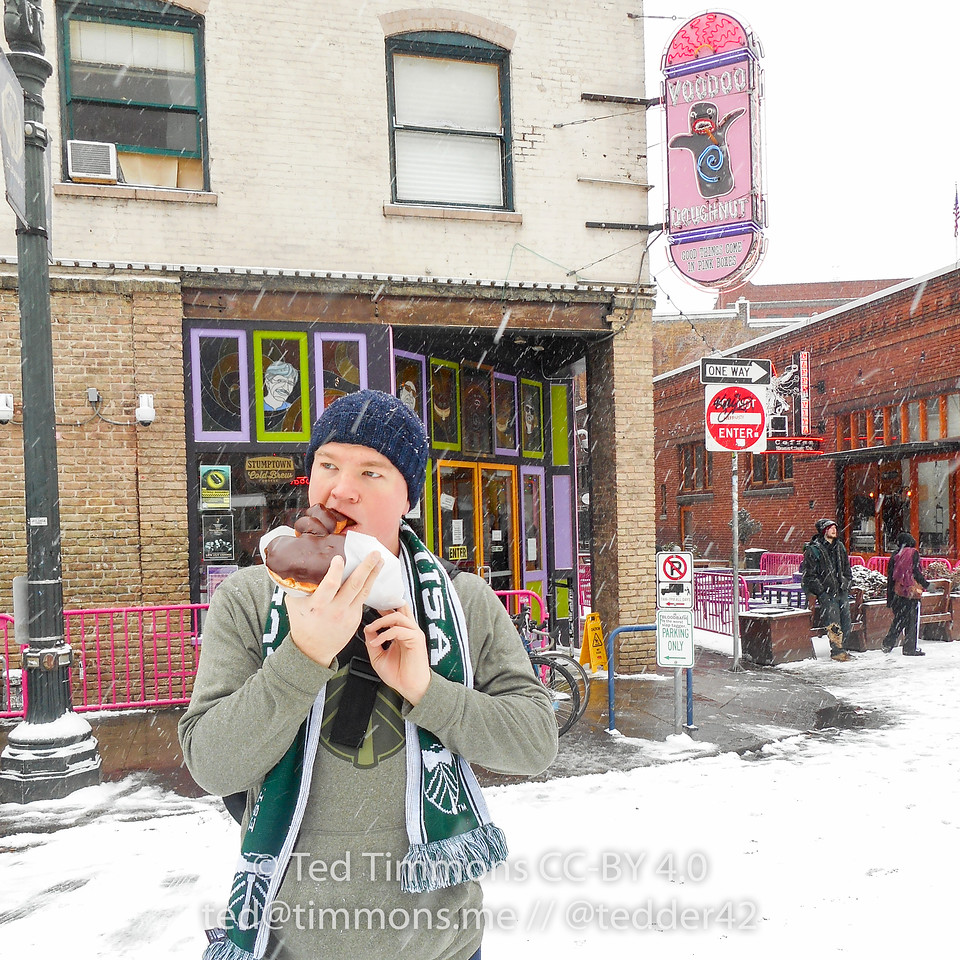 Jeremy, taking a big bite of his Cock and Balls in front of Voodoo donuts. #snowday