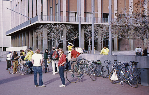 4*Sun, Mar 5, 1972<br /> People: Gunter Hamersbach(legs crossed), Ken Leitch(helmet, yellow),Patty Rose(dark green,<br /> Subject: assemble for bike ride<br /> Place: Bancroft / Telegraph, Sproul Plaza<br /> Activity: <br /> Comments: same as prev photo, but scanned 600 dpi