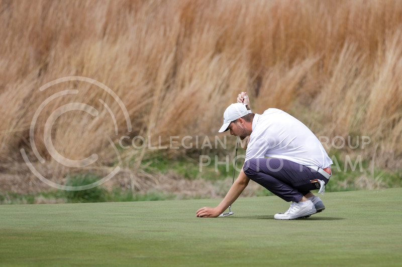 Tim Tillmanns carefully places the ball during the first round of the Big 12 Golf Championship at Prairie Dunes Country Club on April 26, 2021. (Sophie Osborn   Collegian Media Group)
