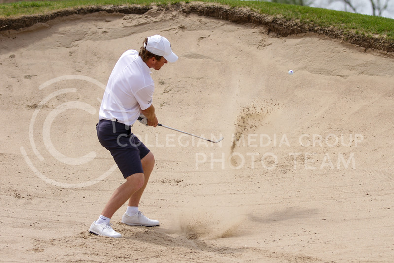 Jacob Eklund hits the ball out of the sand during the first round of the Big 12 Golf Championship at Prairie Dunes Country Club on April 26, 2021. (Sophie Osborn   Collegian Media Group)