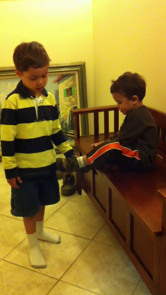 Riley helps little brother take off his socks and shoes!