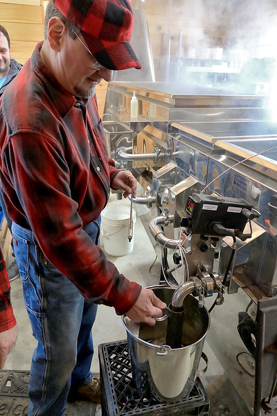 Big Head Fred's Maple Syrup in Leominster was boiling syrup at their sugarhouse for the first time this year on Sunday, March 3, 2019. Employee of David Thibodeau gets some newly made syrup during their first boiling of the season. SENTINEL & ENTERPRISE/JOHN LOVE