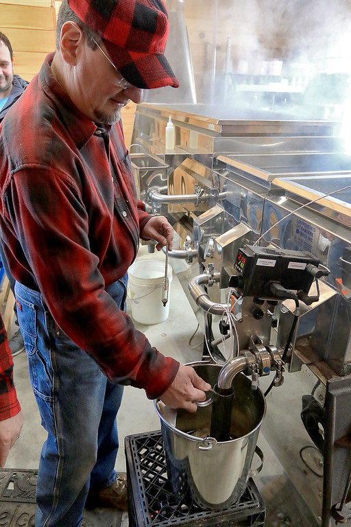 . Big Head Fred\'s Maple Syrup in Leominster was boiling syrup at their sugarhouse for the first time this year on Sunday, March 3, 2019. Employee of David Thibodeau gets some newly made syrup during their first boiling of the season. SENTINEL & ENTERPRISE/JOHN LOVE