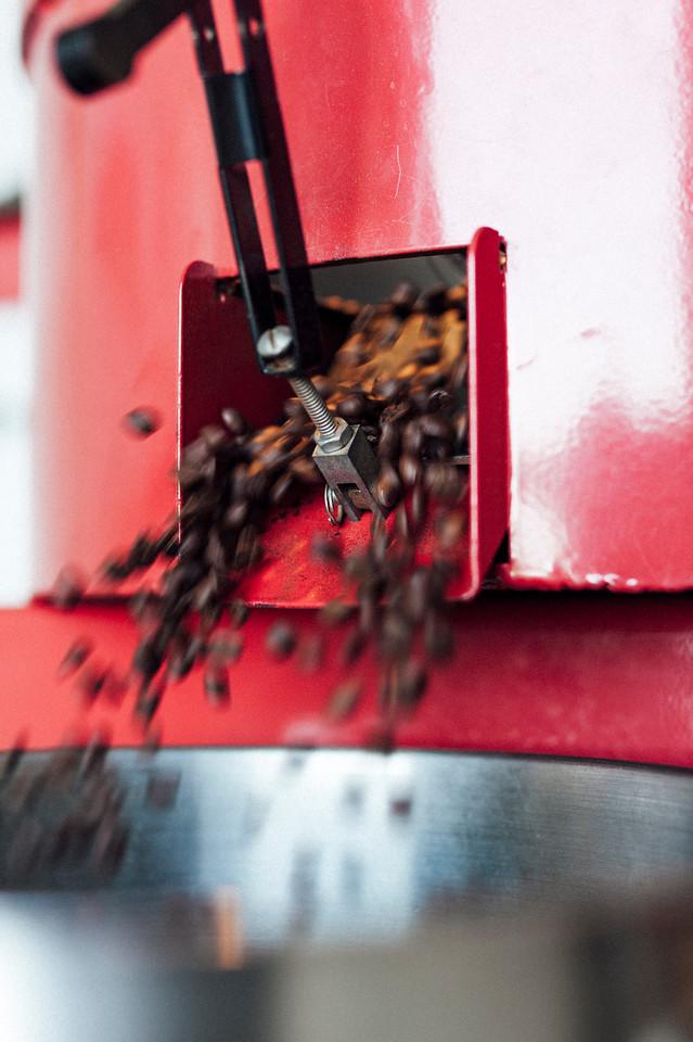 Kona coffee flies out of the roaster at Hula Daddy Kona Coffee.