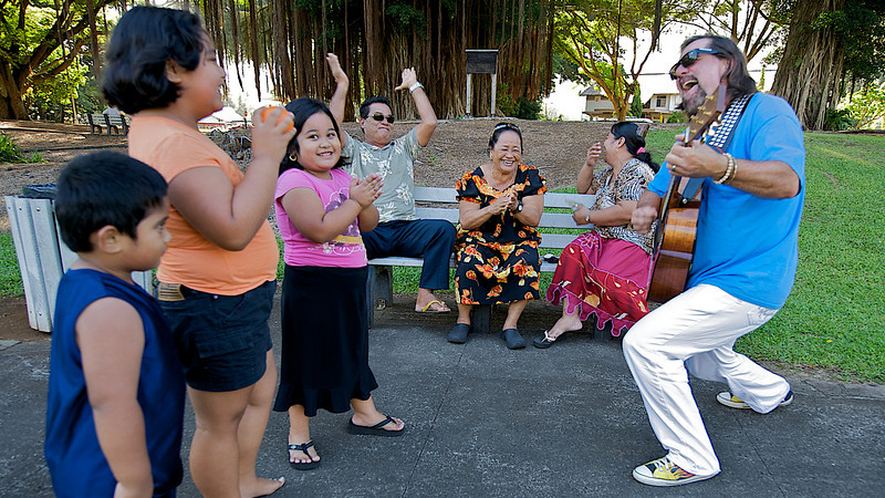 Jerry plays tunes for a family relaxing under a Banyan tree at Queen Liliuokalani Gardens in Hilo  (Photo credit: Patsy Ferrell, ©2009, All rights reserved)