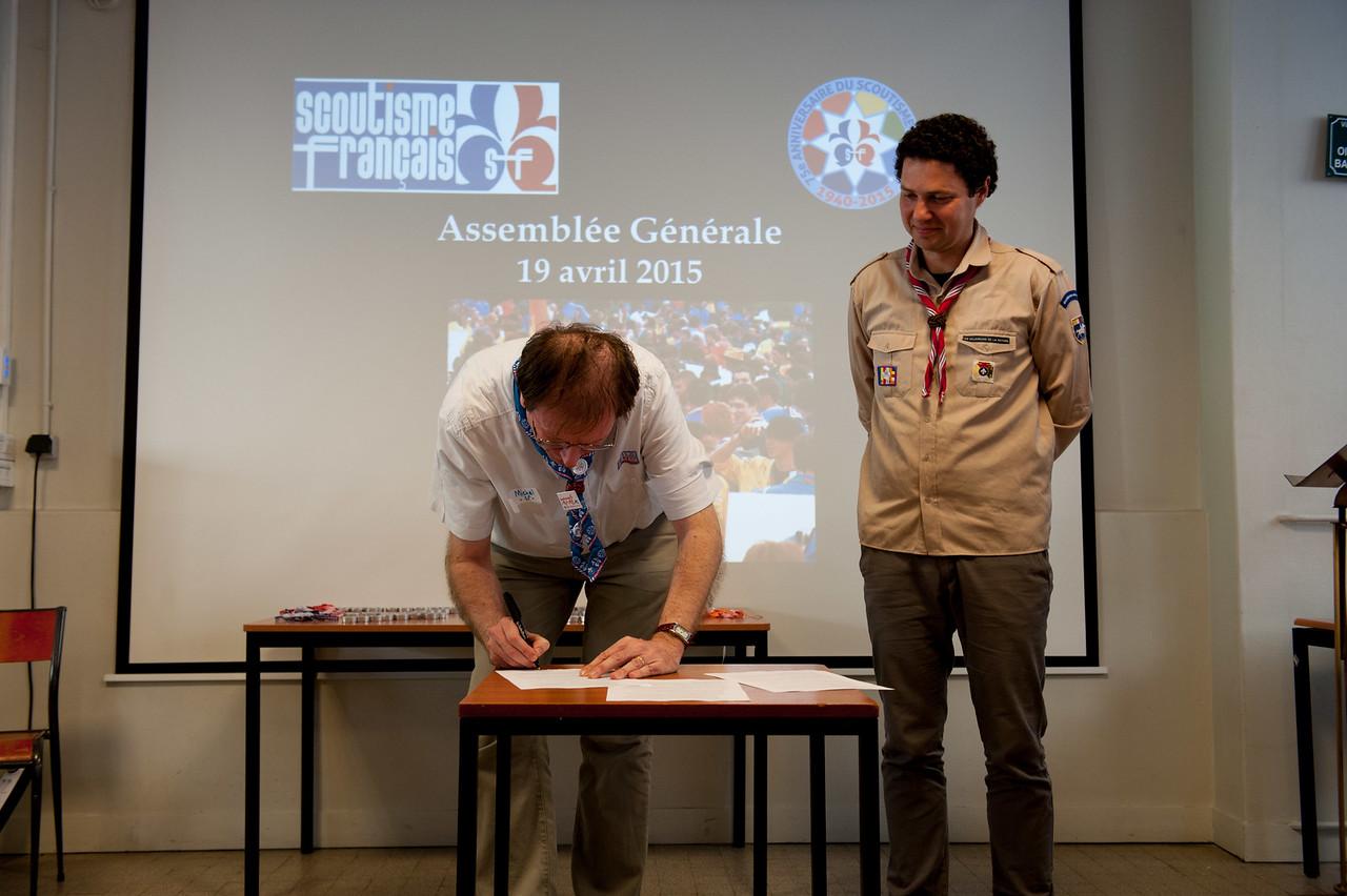 Michel appose sa signature en tant que président du Scoutisme Français.