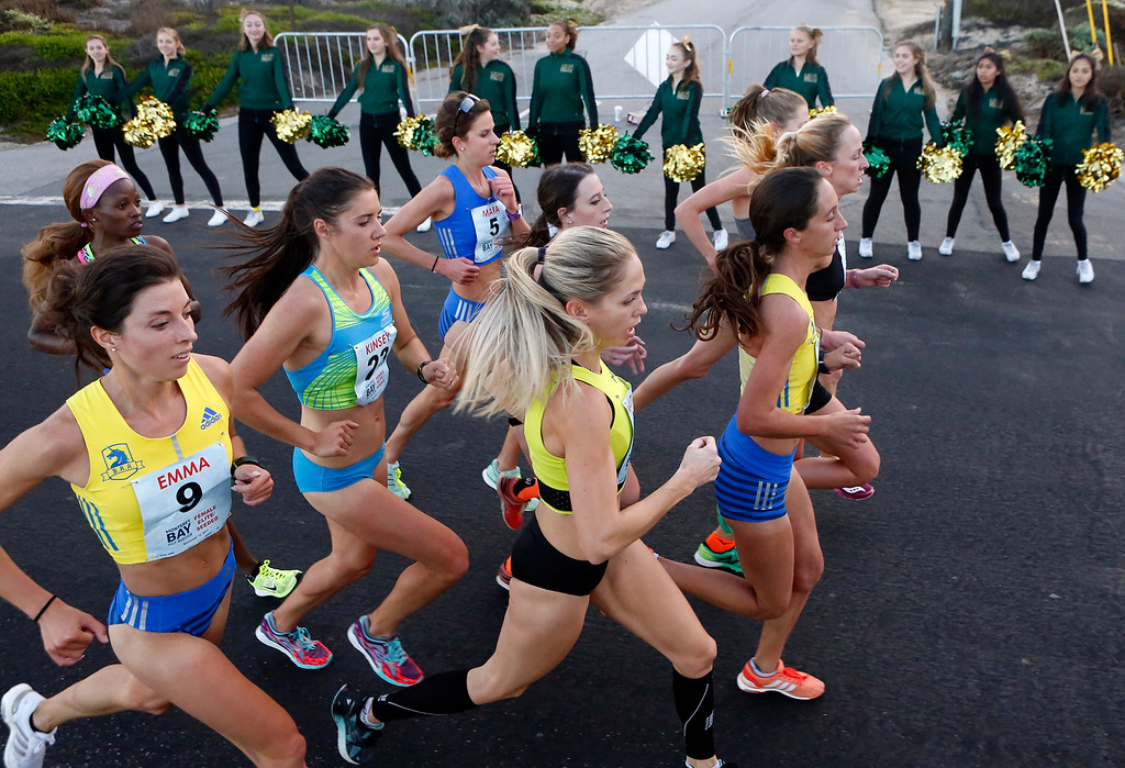 . The lead pack of female runners pass a line of Monterey High School cheerleaders  along Ocean View Boulevard during the Monterey Bay Half Marathon in Pacific Grove, Calif. on Sunday November 12, 2017. (David Royal/Herald Correspondent)