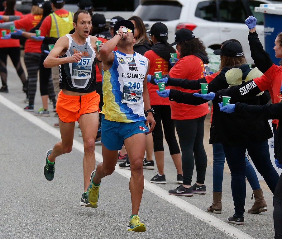. Jorge Maravilla leads Adam Roach through a water station at Big Sur Village during the Big Sur Marathon on Sunday April 29, 2018. Roach won the race, Maravilla took second. (David Royal/ Herald Correspondent)