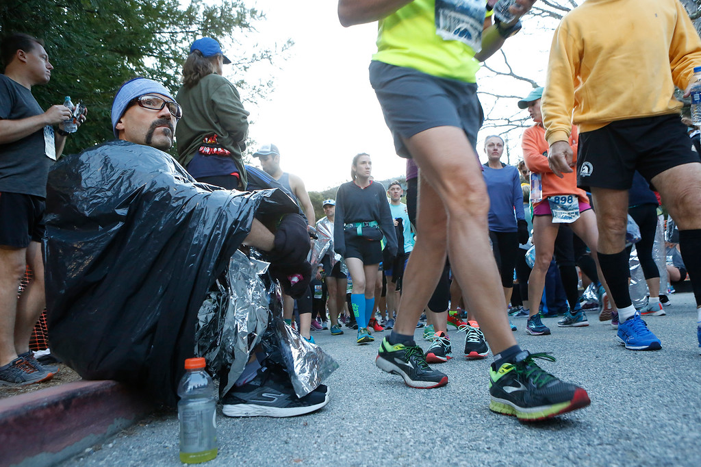 . Travis Prater of Corpus Christi, TX warms up under a trash bag before the start of the Big Sur Marathon in Big Sur, Calif. on Sunday April 29, 2018. (David Royal/ Herald Correspondent)