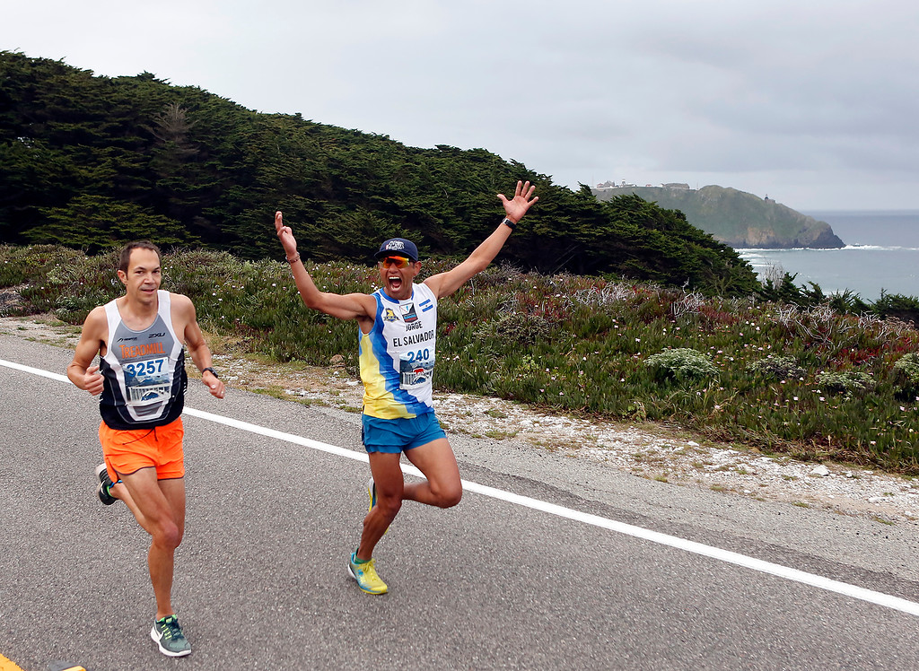 . Jorge Maravilla of Mill Valley, throws his arms in the air beside Adam Roach, of Pebble Beach run past Point Sur during the Big Sur Marathon in Big Sur, Calif. on Sunday April 29, 2018. Roach won the race, Maravilla took second. (David Royal/ Herald Correspondent)