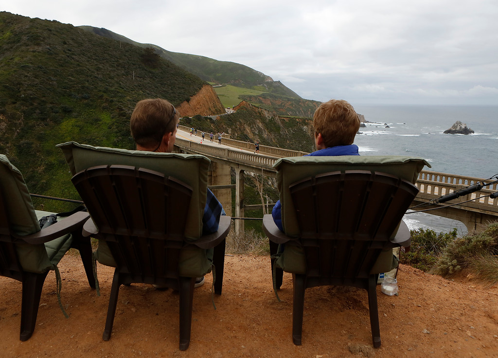 . A couple watch runners run over Bixby Bridge during the Big Sur Marathon in Big Sur, Calif. on Sunday April 29, 2018. . (David Royal/ Herald Correspondent)