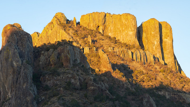 Casa Grande Sunrise<br /> Big Bend National Park<br /> Texas<br /> 2013<br /> <br /> Casa Grande at sunrise is one of those mental images that stick in your mind.  I especially like the way that the trees on the shadowed hill (mid left) contrast with the brightly illuminated rock wall behind them.  This is a very hard image to print to complete satisfaction.  There is a lot of detail in this image but dealing with the strong darks and bright components is a real challenge.  It was taken of the 2013 trip that Coralie and I made together to Big Bend - her first trip.<br /> <br /> A print of this image hangs over the fireplace in our living room.   It is one of my favorite Big Bend images.