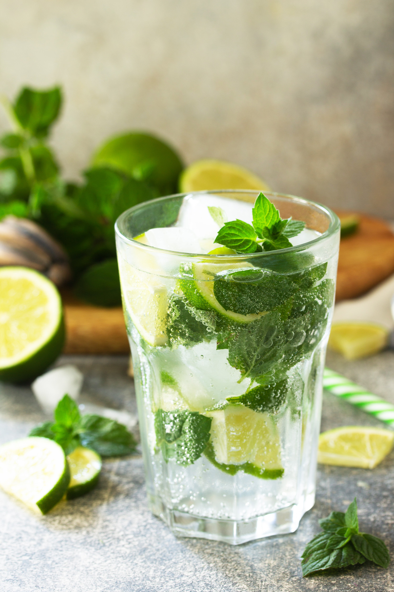 Cuban mojito cocktail with lime and mint in the background.