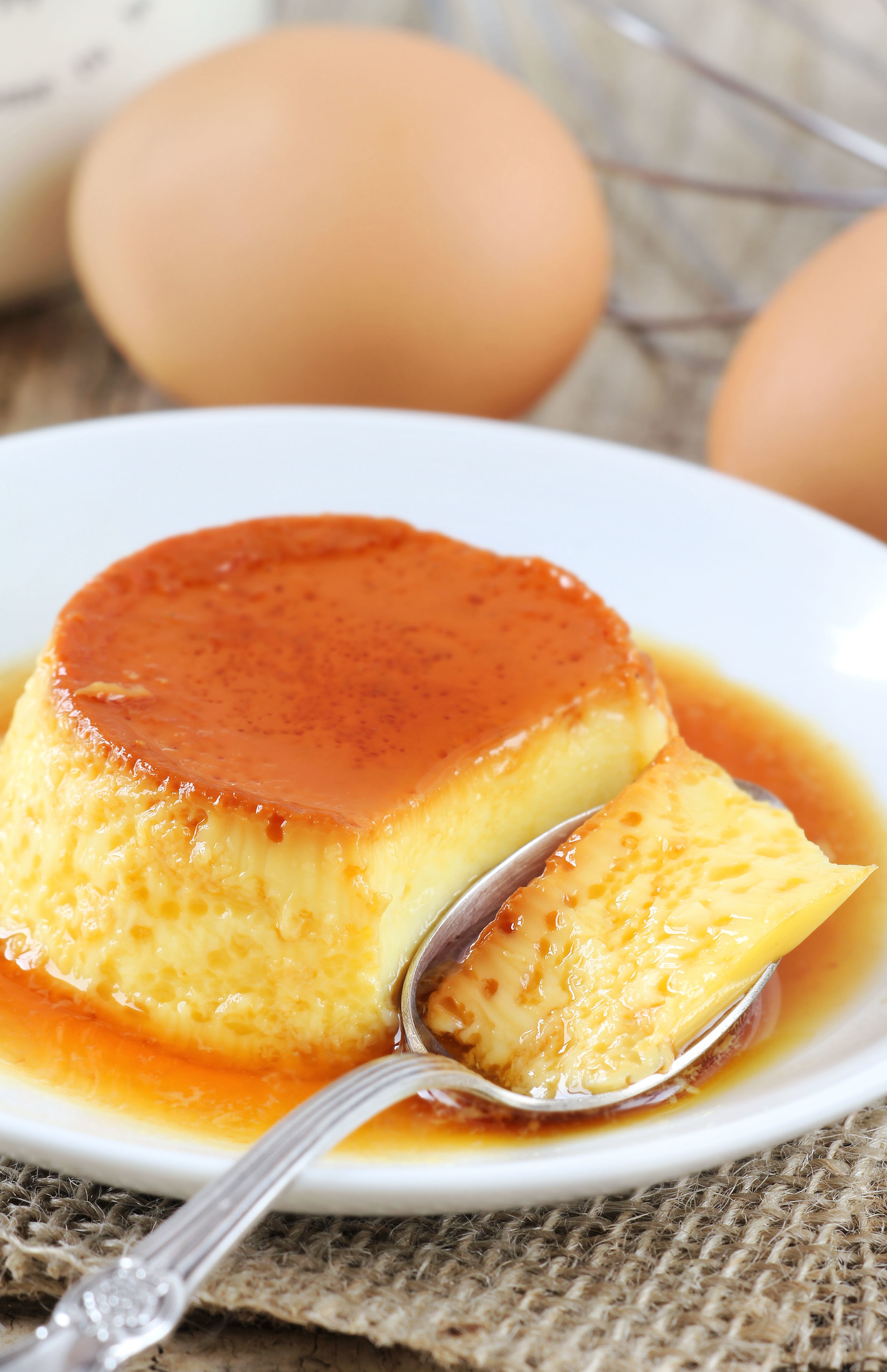 Flan Cubano on a white plate with eggs behind it.