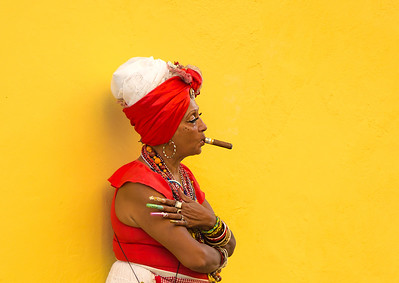 HAVANA-CUBA- DEC 4, 2018:  Woman with a cigar in her mouth with a yellow background letting tourists