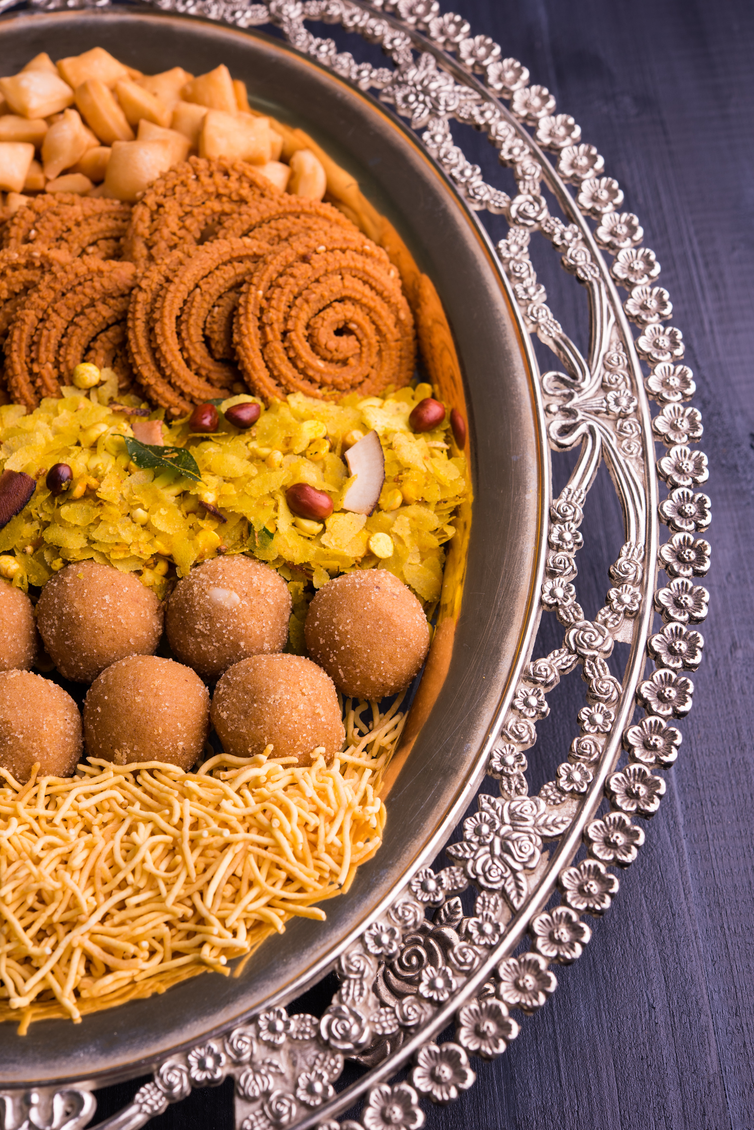Plate of Diwali food on dark grey background.