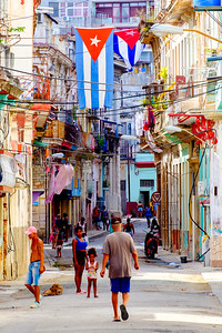 HAVANA,CUBA - SEPTEMBER 29,2018 : Urban scene with cuban flags, people and aged buildings in Old Hav